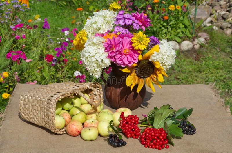 Basket with apples anda bouquet of flowers on the table in the garden royalty free stock photography