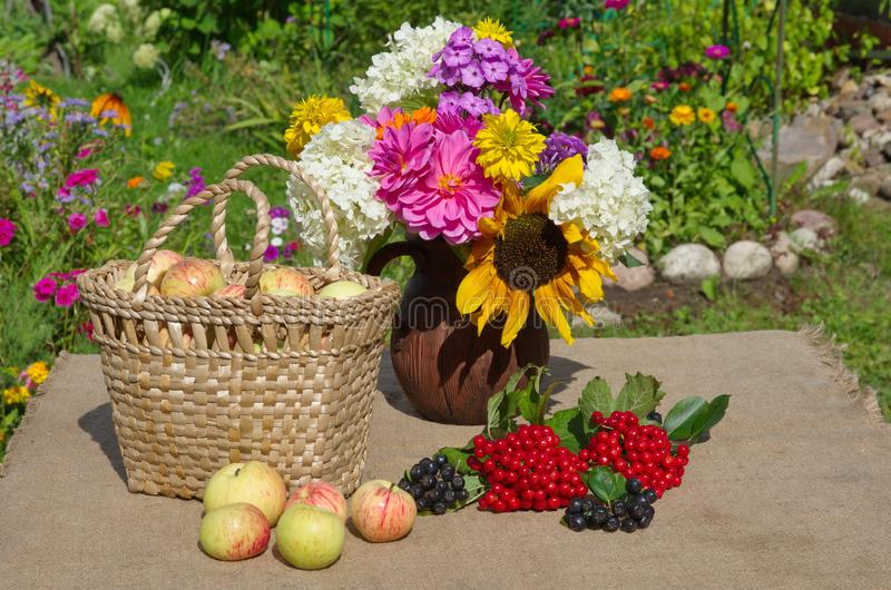 Basket with apples and a bouquet of flowers stock image