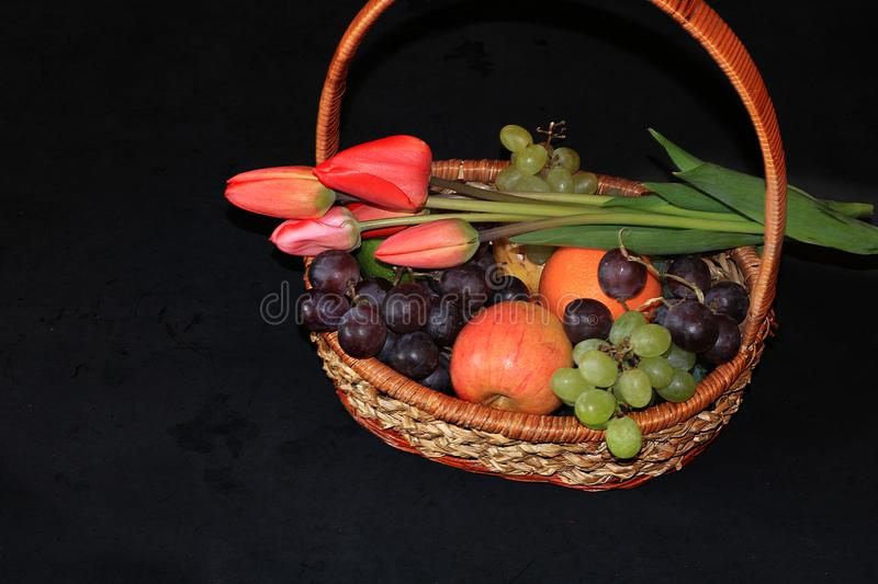Basket with apples, tulips and grapes on a black background, selective focus. stock image