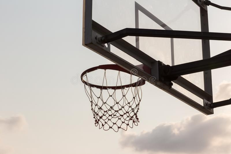 basket ball board under sky with white clouds. Basketball court with old backboard. sky and white clouds on background. stock photography