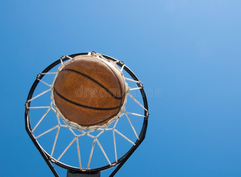 Basket-ball en cieux bleus d'agaisnt net image libre de droits
