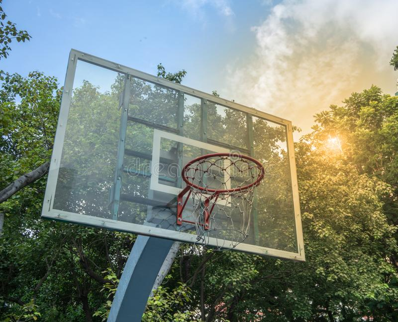A basket ball hoop in public park with green trees and blue sky. Background stock photography