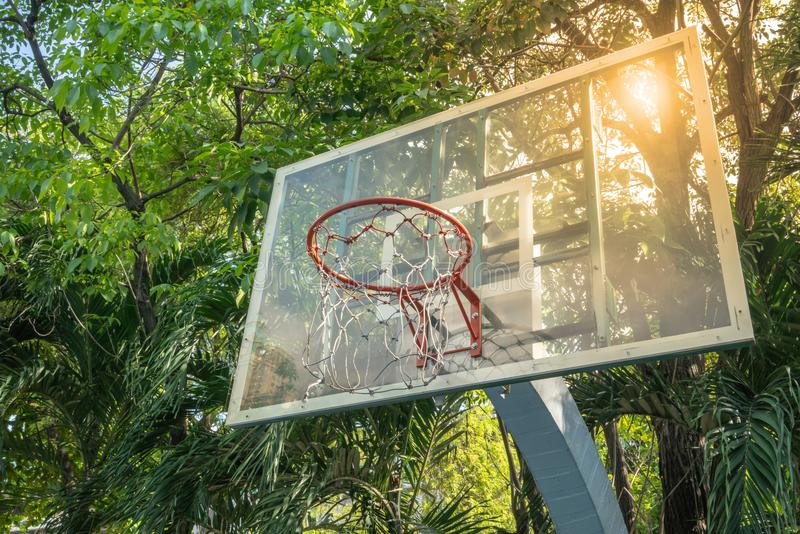 A basket ball hoop in public park with green trees and blue sky. Background stock images