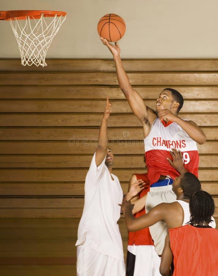Basket-ball trempant de joueur de basket dans le cercle images stock