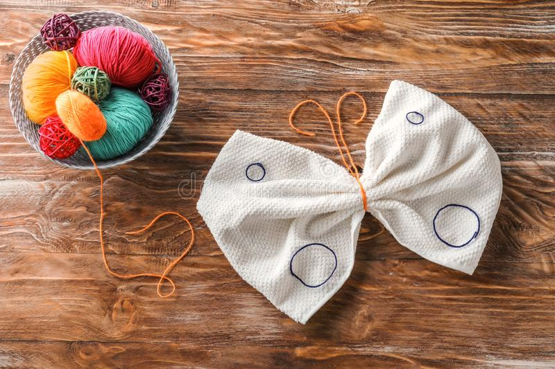 Basket with balls of knitting yarn and butterfly made of towel and thread on wooden table royalty free stock image