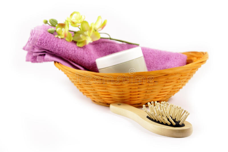 Basket with beauty and hygiene products. Towel, brush and cream pot royalty free stock photo