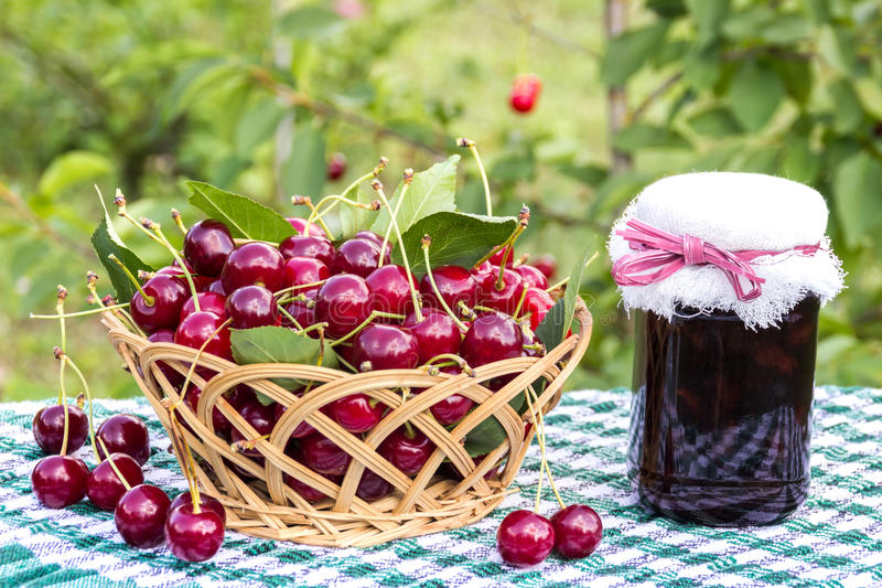 Download Basket Of Cherries And Cherry Jam Jar On  Background Of Cherry Tree Stock Photo - Image: 83724485