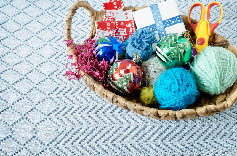 Basket Christmas crafts. Skeins of yarn and Christmas balls in a basket stock photo