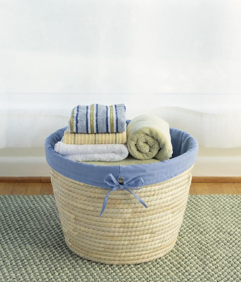 Basket of clean, cotton towels linens laundry. Home housework chores housekeeping cleaning royalty free stock image
