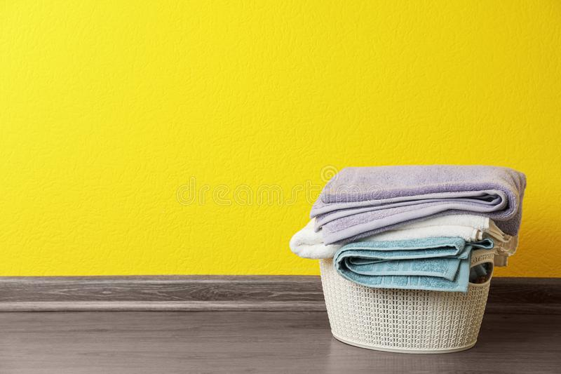 Basket with clean laundry on floor near yellow wall, space for. Text royalty free stock images