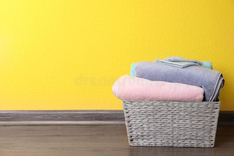 Basket with clean laundry on floor near yellow wall. Space for text stock image
