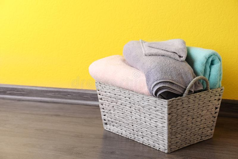 Basket with clean laundry on floor near yellow wall, space for. Text stock images