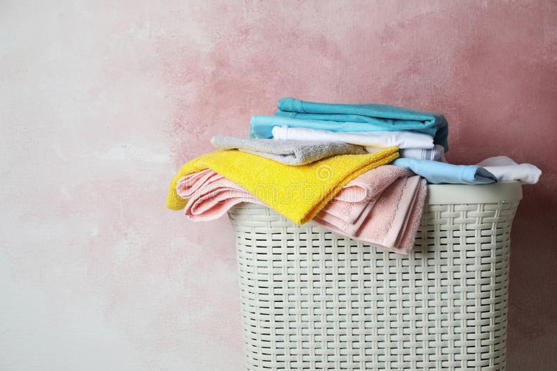 Basket with clean laundry on pink background, space for. Text stock photo