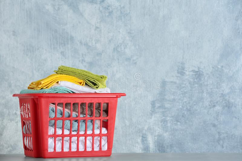 Basket with clean laundry on table, space for text. Basket with clean laundry on table against color background, space for text royalty free stock photos
