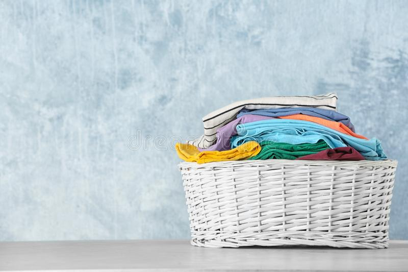 Basket with clean laundry on table against color background. Space for text royalty free stock photography