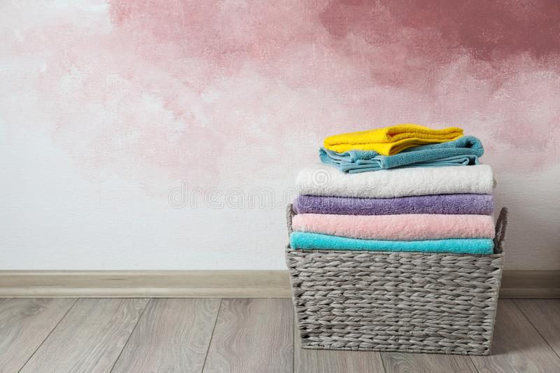 Basket with clean laundry on wooden floor near pink wall, space for. Text stock image
