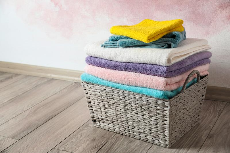 Basket with clean laundry on wooden floor near pink wall. Space for text royalty free stock photos