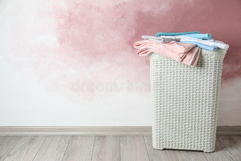 Basket with laundry on wooden floor near pink wall, space for text. Basket with clean laundry on wooden floor near pink wall, space for text stock image