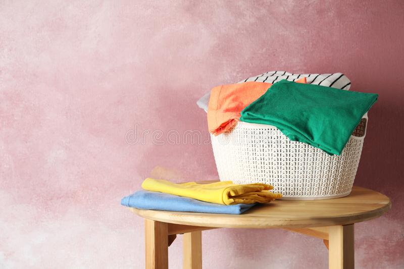 Basket with clean laundry on wooden table near pink wall, space for. Text stock photo