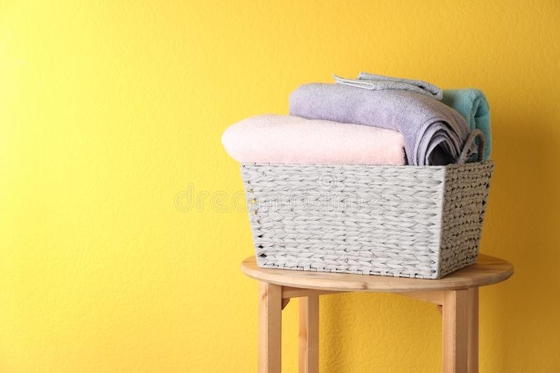 Basket with clean laundry on wooden table near yellow wall, space for. Text stock photography