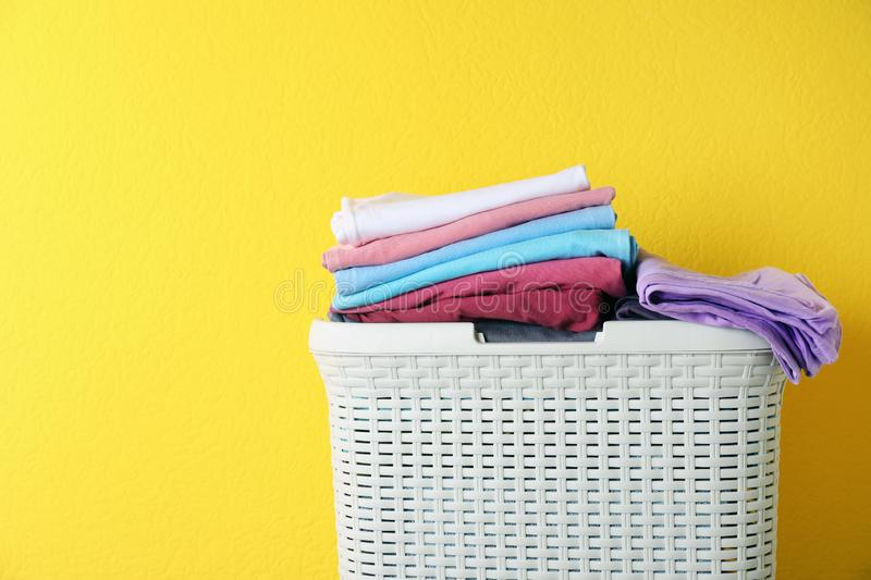 Basket with clean laundry on yellow background. Space for text stock images