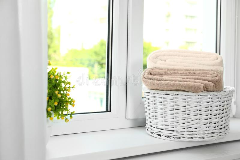 Basket with clean soft towels on window sill. Space for text royalty free stock photo