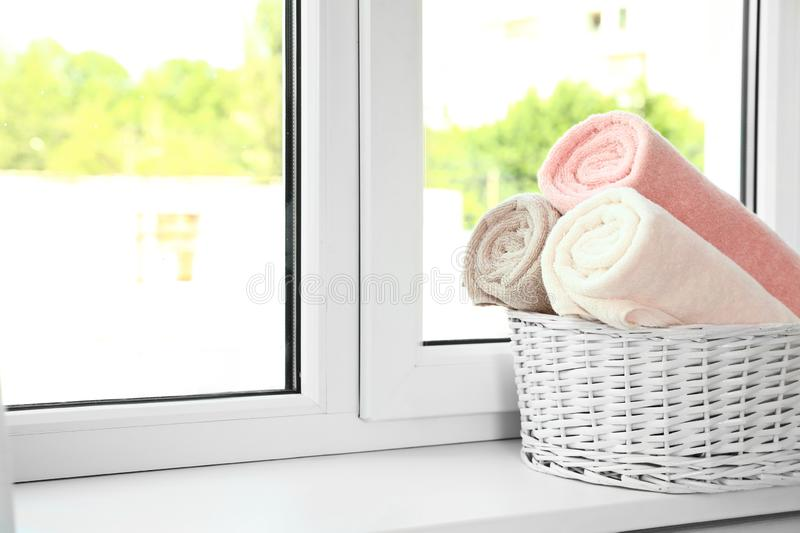Basket with clean soft towels on window sill. Space for text stock photography