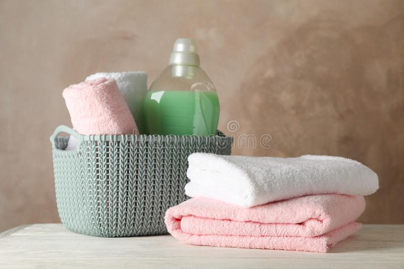 Basket with clean towels and laundry liquid on wooden background. Space for text royalty free stock images