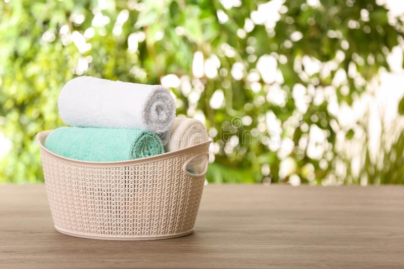 Basket with clean towels on table against blurred background. Space for text stock photo
