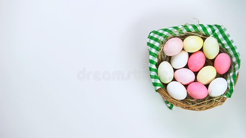 Basket of colored Easter eggs standing on white table, holiday celebration royalty free stock image
