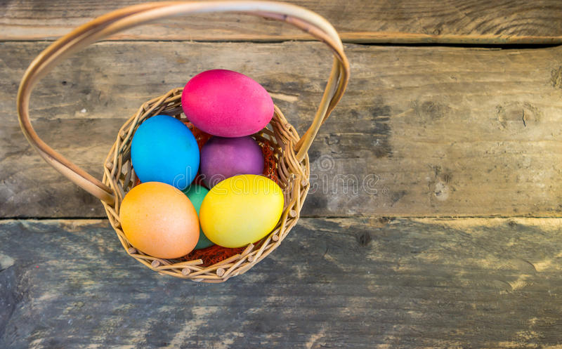 Basket with colorful easter eggs on wooden table . Happy Easter royalty free stock photo