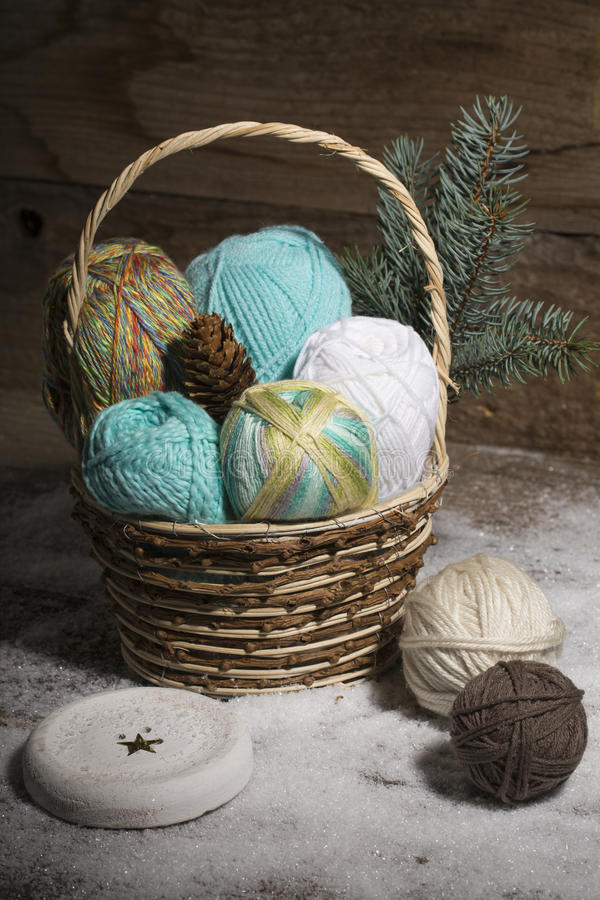 Basket with colorful yarns decoarted with pine brunch royalty free stock images