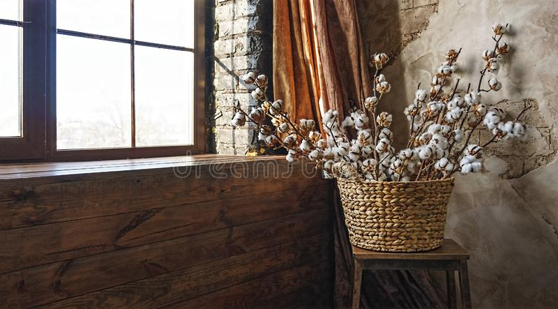 , , , Basket, cotton branches, loft interior, brick wall royalty free stock images