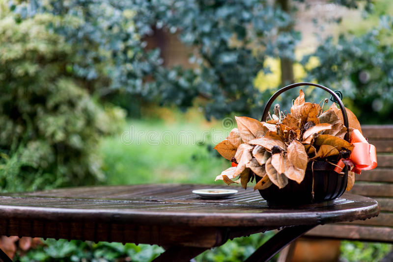 Basket of Dead Flowers On A Wet Wooden Table. In A Garden royalty free stock images