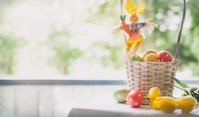 Basket of decorated eggs with yellow tulips next window stock image