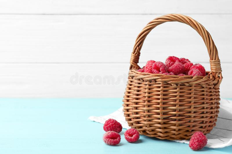 Basket of delicious fresh ripe raspberries on blue wooden table against white background, space for stock photos