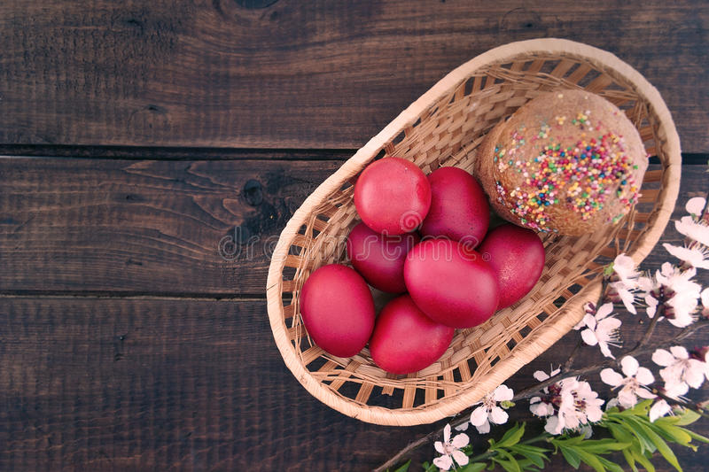 Basket with easter cake and red eggs on rustic wooden table. Top royalty free stock photos