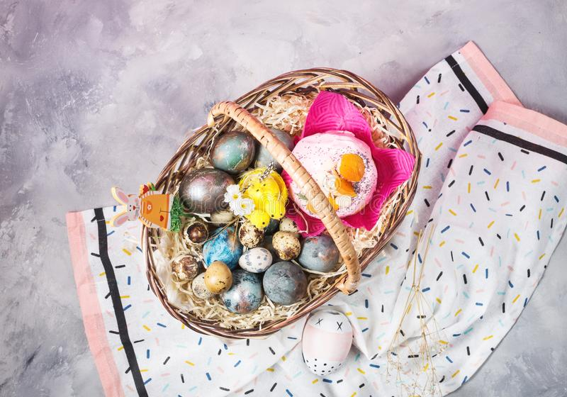 Basket with easter cakes and painted eggs on concrete background. Easter concept royalty free stock photography