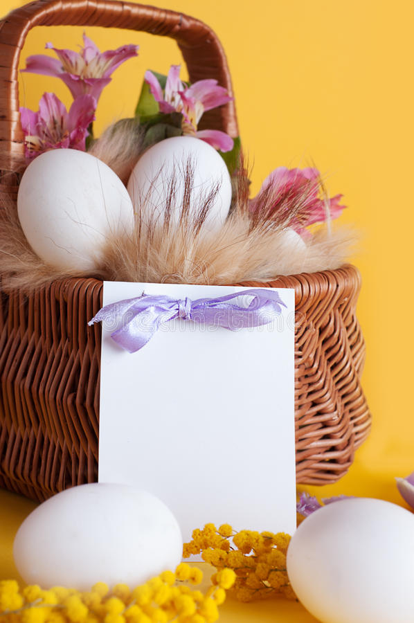 Basket of eggs and spring flowers stock photography