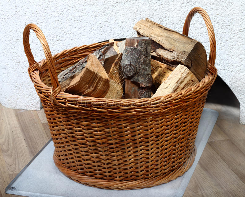 Basket of firewood. Wicker basket of firewood on the floor near white oven stock images
