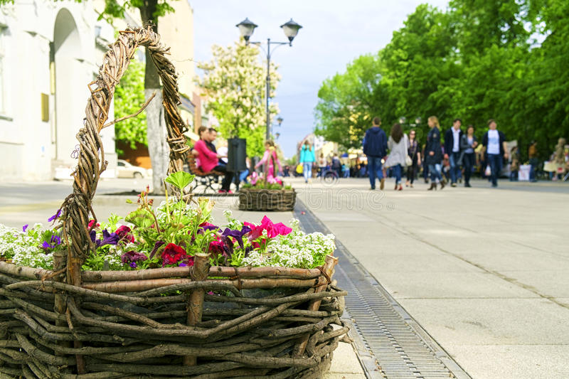 Basket with flowers on the city street. Walking people. royalty free stock photo
