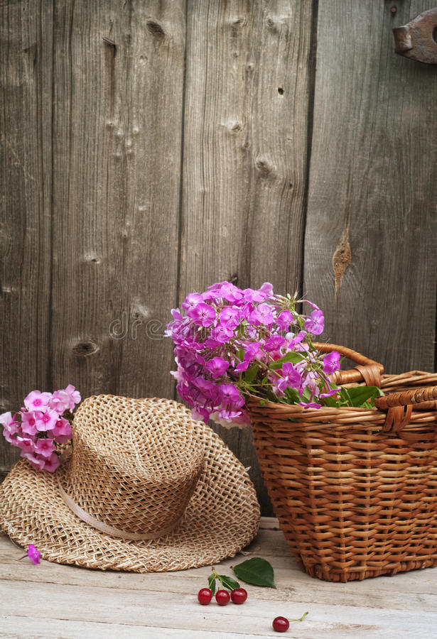Basket of flowers and a straw hat stock photo