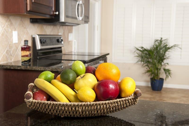 Basket of fresh fruit in modern kitchen stock photos