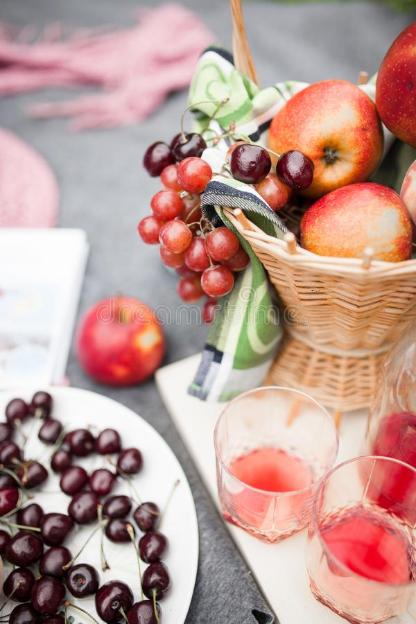 A basket of fresh fruit on a rug with glasses of booze stock images