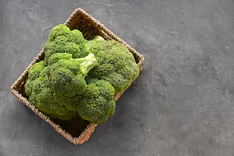Basket with fresh green broccoli on grey table stock images