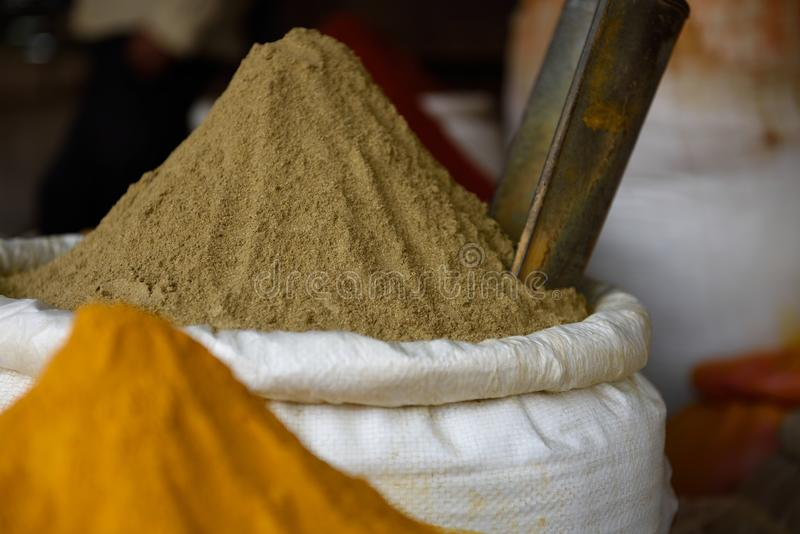 Basket of fresh ground raw Indian coriander powder, or dhania,. In a spice market in Jaipur, Rajasthan, India royalty free stock photo
