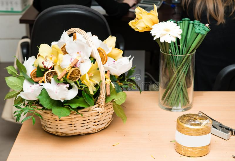 basket of fresh orchid flowers on table stock image