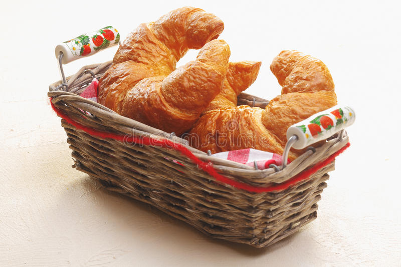 Basket of freshly baked croissants. Basket of freshly baked golden crescent-shaped croissants on a white tabletop to serve as an accompaniment to a meal royalty free stock photography