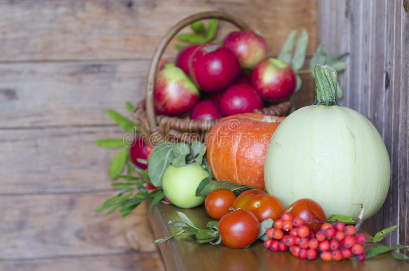 Basket with fruits on a wooden background. harvesting autumn and summer harvest. vegetables and fruits pumpkin, zucchini, apple,. Rowan, pea, cherry. soft focus royalty free stock photos