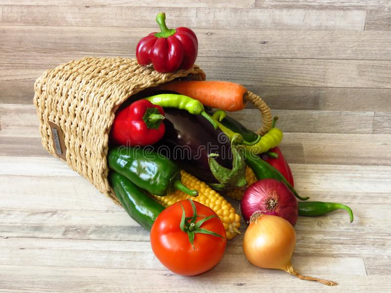 Summer organic vegetables for salad. Basket on vegetables on light wood background. Basket full of juicy organic green red peppers, red tomato, purple eggplant royalty free stock photos